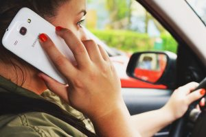 photograph of a woman on the phone while driving