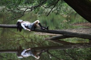 Photograph of a girl lying on a tree branch above a lake, sleeping with a book on her face.